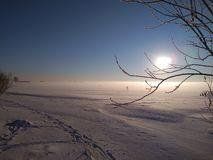 Sunny winter day on the Bay. Photo sunny winter day on the Bay. The sun against the blue sky. Footprints in the snow royalty free stock photography