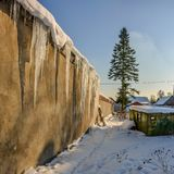 Sunny winter day in the countryside. The sign of winter-icicles Royalty Free Stock Photo