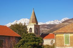 Sunny winter day in Mediterranean village. Red roofs and bell tower against blue sky and snowy mountain. Montenegro, Tivat royalty free stock photo
