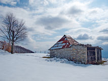 Sunny, winter day with snow and a lonely mountain cottages Royalty Free Stock Photography