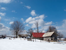 Sunny, winter day with snow and mountain cottages Royalty Free Stock Image
