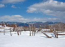 Sunny, winter day with snow and old mountain fences Stock Image