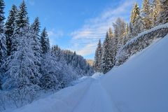 Road in the Winter Forest in the Ural Mountains, Russia, Chelyabinsk region, Minyar. Pushkin`s fairy tal. Sunny winter day in the Ural Mountains, Russia Stock Photo