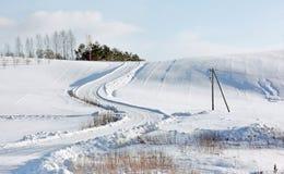 Sunny Winter Landscape mit einer Straße, die auf einen Hügel geht Lizenzfreies Stockfoto