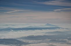 Sunlit blue ridges, misty valleys under cloud stripes in winter. Sunny winter panoramic landscape with blue mountain ridges, misty valleys and conical Velky Choc royalty free stock photo