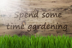 Sunny Wooden Background, Gras, Text Spend Some Time Gardening. English Text Spend Some Time Gardening. Spring Season Greeting Card. Sunny Aged Wooden Background Stock Photography