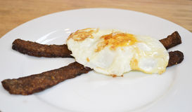 Sunnyside down egg on meatless bacon Royalty Free Stock Photos