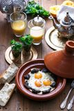 Sunnyside Eggs cooked in a Tajine dish with beef, Moroccan breakfast with juice and mint tea.  Stock Photos