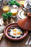 Sunnyside Eggs cooked in a Tajine dish with beef, Moroccan breakfast with juice and mint tea.  Stock Image