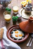 Sunnyside Eggs cooked in a Tajine dish with beef, Moroccan breakfast with juice and mint tea.  Royalty Free Stock Images