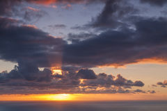 Sunray Clouds. Seascape showing sunset with strong sun ray shining through clouds Royalty Free Stock Image