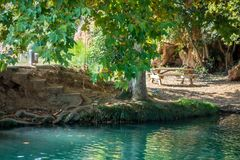 Sunray makes its way through the leaves to the water at Gorgo Catalán. Sunray makes its way through the leaves to the turquoise water at Gorgo Catalán stock photo