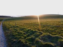 Sunray over green field. Sunray over the green path looking down on the water of the river stock photography