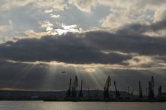 Sunray over Varna port. Silhouette of cranes royalty free stock images