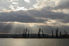 Sunray over Varna port. Silhouette of cranes stock images