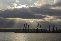 Sunray over Varna port. Silhouette of cranes royalty free stock photography