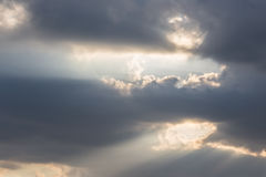 Sunrays and clouds. A close up of some dark clouds with powerful sunrays cutting through some holes Royalty Free Stock Image