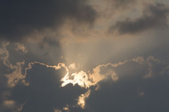 Sunrays and clouds on grey sky backgrounds Royalty Free Stock Image