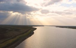 Sunrays through Clouds spreading over a River Stock Photo