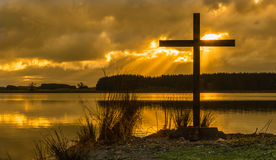 Sunrays Cross. Black cross by a lake with sun rays shining through clouds Stock Images