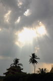 Sunrays and dark clouds over palm trees. The sky is dark, it is stormy, and hard rain is falling over Shwemawdaw Pagoda, Bago, Myanmar. Sun rays dramatically Royalty Free Stock Photo