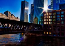 Sunrays extend over Chicago downtown during morning commute on a late February winter evening. El train passes over Chicago River. Royalty Free Stock Photos