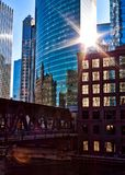 Sunrays extend over Chicago downtown during morning commute on a late February winter evening. El train passes over Chicago River. Stock Photos