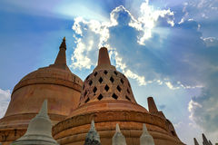 Sunrays shining through clouds above Chedi Hin Sai at Wat Pa Kung Temple, Roi Et, northeastern Thailand Royalty Free Stock Image