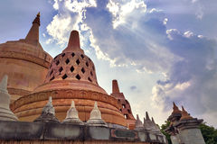 Sunrays shining through clouds above Chedi Hin Sai at Wat Pa Kung Temple, Roi Et, northeastern Thailand Stock Images