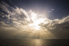 Sunrays at sunset with clouds. Stock Photo