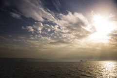 Sunrays at sunset with clouds. Royalty Free Stock Photography