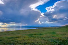 Sunrays thru stormy clouds. Sun rays shining thru stormy clouds at Song Kul lake, Kyrgyzstan Stock Image