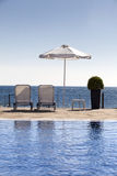 Sunregenschirm und -stühle nahe einem Pool Lizenzfreie Stockbilder