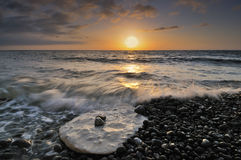 Sunrise. On the beach with waves that washed over the rocks Stock Photography