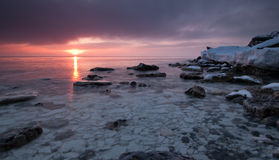 Sunrise. At the beach with rocks and ice Stock Photo
