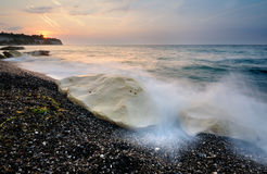 Sunrise. At the beach with a wave that washes over some rocks Royalty Free Stock Images