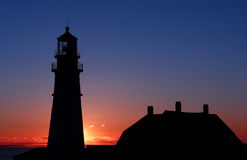 SUNRISE. A quiet and lovely sunrise at Portland Head Light with beautifully illuminated clouds, and lovely silhouette of this lighthouse, the most photographed Royalty Free Stock Photos