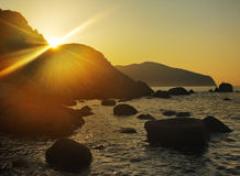 Sunrise. The sun ascends because of a rock over the sea Royalty Free Stock Photo