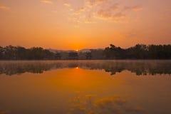Sunrise. Over  the foggy lake and pavllions Royalty Free Stock Photo