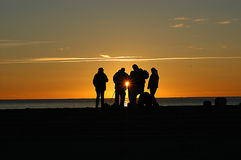 Sunrise. People on the beach at sunrise. Sun flare visibile in the center of the image Stock Photography
