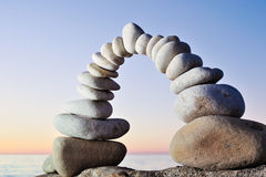 Sunrise. Arch of the white pebbles on the coast in the morning Stock Photos