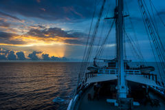 Sunrise Aboard a Traditional Phinisi Schooner. A beautiful sunrise while sailing through the Raja Ampat area of eastern Indonesia. Dramatic skies and sun rays Royalty Free Stock Photo