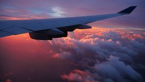 Sunrise above the airplane wing. A beautiful sunrise above the clouds and airplane wing stock photo