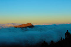 Sunrise above the clouds which illuminates the top of a mountain in Tenerife Island. Canary. Span, Europe. Beautiful sunrise above the clouds which illuminates stock images