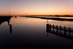Sunrise above a dutch river. Beautiful sunrise above a dutch river while a ship is approaching royalty free stock photos