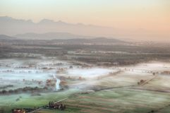 Sunrise above fields covered with morning mists Stock Photography