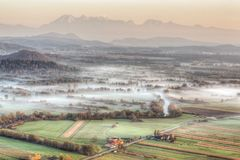Sunrise above fields covered with morning mists Stock Photos