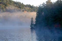 Sunrise above forest lake Stock Photo