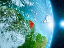 Sunrise above French Guiana on planet Earth. French Guiana from orbit of planet Earth with clouds during sunrise with highly detailed surface textures. 3D Stock Photos