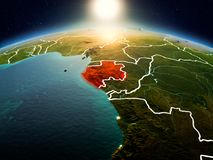 Gabon in sunrise from orbit. Sunrise above Gabon highlighted in red on model of planet Earth in space with visible country borders. 3D illustration. Elements of Royalty Free Stock Image